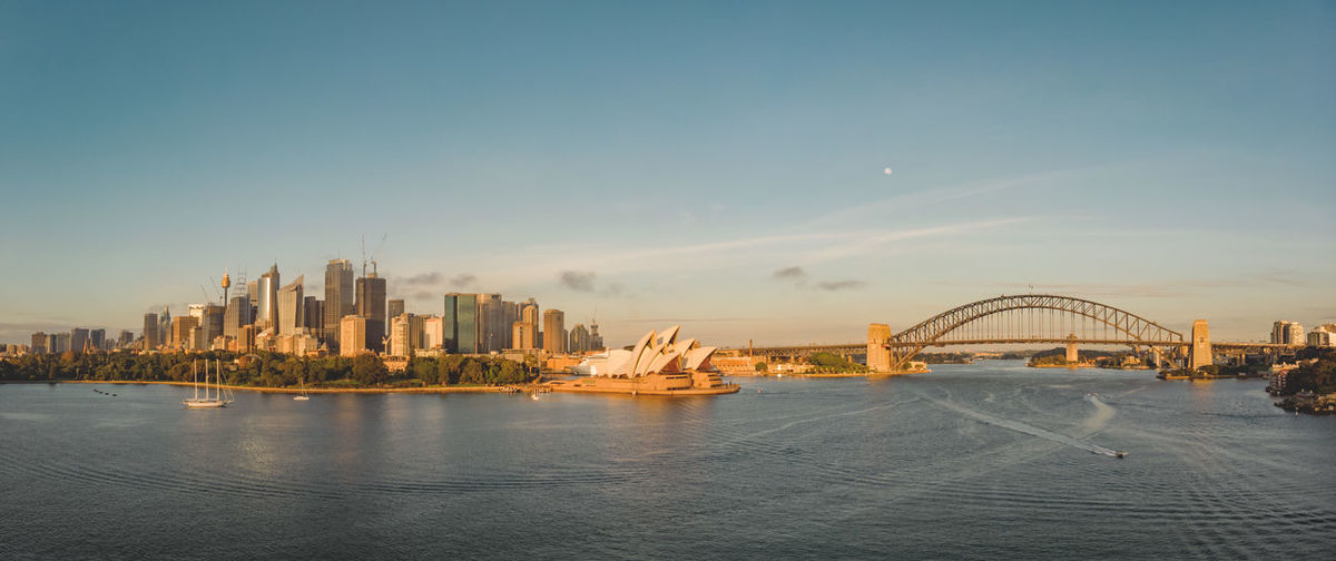 Drone panorama aerial of the Sydney city skyline with Opera House and Harbour Bridge early morning during sunrise. Built Structure City Sky Water Bridge - Man Made Structure Connection Bridge Skyscraper Cityscape Building Waterfront Urban Skyline Travel Destinations Financial District  Sydney Skyline Sydney Harbour Bridge Sydney Opera House Sun Dawn Sunlight Panorama Drone  Aerial View Travel Tourism Architecture Transportation Landscape No People Outdoors Bay Harbor Discover Your City Discover Places Harbour Bridge Opera House Australia Moon Full Moon Boat Sailing Soft Light Dji DJI Mavic Air Highrise Harbour Harbourside Urban Morning