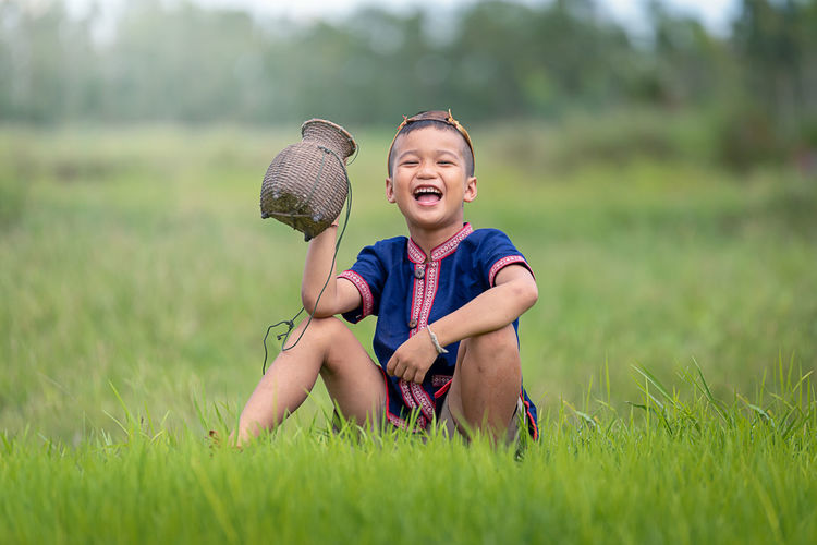 Childhood Child Plant Sitting Happiness Casual Clothing Males  Field Day Men Emotion Grass Full Length Smiling Leisure Activity Innocence Front View Land One Person Outdoors Shorts