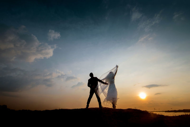 Rear View Of Bride And Groom Standing On Field Against Sky During Sunset