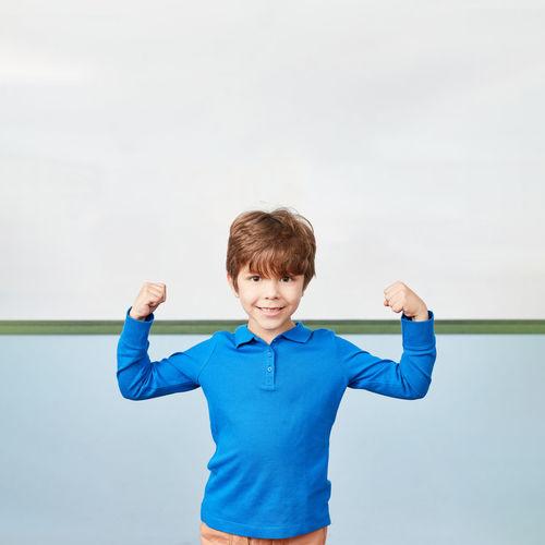 Full length of boy standing against blue sky