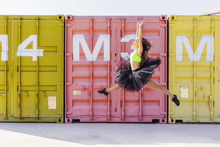 Ballet dancer dancing against cargo containers