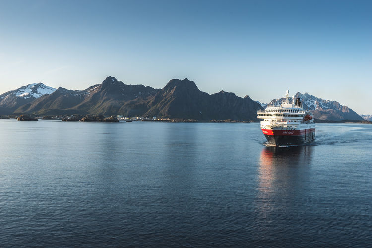 Beauty In Nature Blue Boat Clear Sky Copy Space Day Journey Lofoten Lofoten Islands Mode Of Transport Mountain Mountain Range Nature Nautical Vessel No People Non-urban Scene Norway Remote Scenics Sea Tranquil Scene Tranquility Transportation Water Waterfront