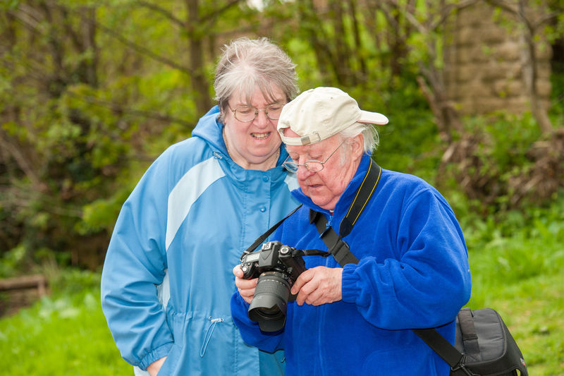 Man photographing woman holding camera while standing outdoors