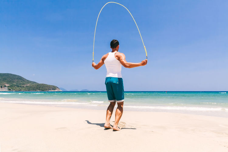 man skipping on beach with sea view. Training outdoors on beach Beach One Person Sand Sea Ocean Fitness Fitness Training Outdoors Man Males  Strong Yoga Stretching Workout Sport Leisure Activity Lifestyles Relaxing Exercising Turquoise Colored Casual Clothing Skipper Skipping Standing