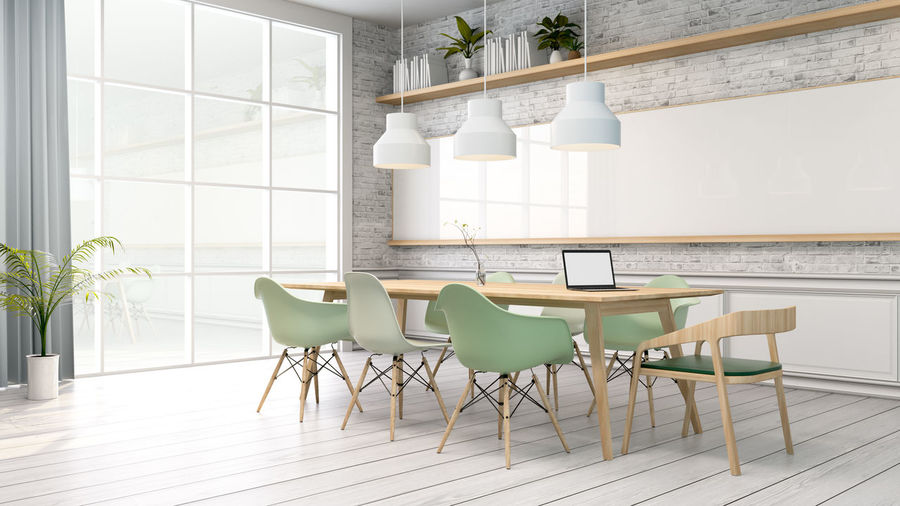 Pendant Lights Hanging Over Table Amidst Chairs At Home