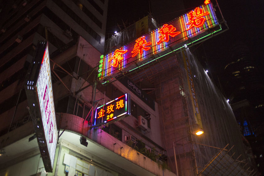 Hong Kong HongKong Advertisement Architecture Building Building Exterior Built Structure City Commercial Sign Communication Illuminated Information Information Sign Lighting Equipment Low Angle View Neon Night No People Outdoors Sign Store Sign Text Western Script