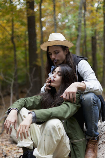 Young couple sitting on tree in forest