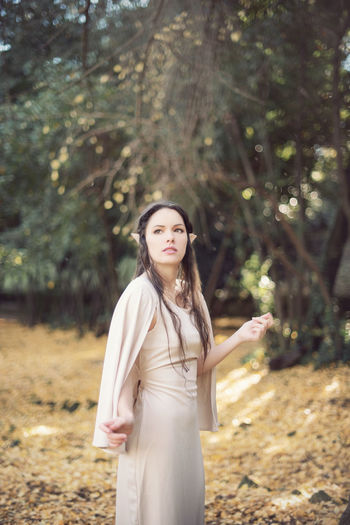 Thoughtful fairy elf young woman standing by trees during autumn