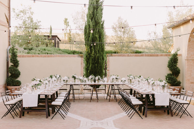 Empty chairs and tables against plants