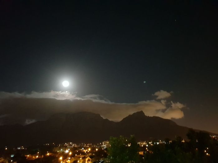 Can Anyone Tell Me What The Blue Object On The Right Hand Side Of The Mountain Is.? There Is No Filter Or Flash Used In This Pic. Clouds Moon City Mountain Illuminated Sky Full Moon Moonlight