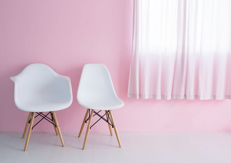 Close-up of empty chair on table against wall at home