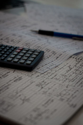 Studying Physics Assignments Physics Text Writing Book Calculator Close-up Education Homework Indoors  Mathematics No People Note Pad Paper Paper Currency Paperwork Pen Pencil School Selective Focus Study Studying Table Universty