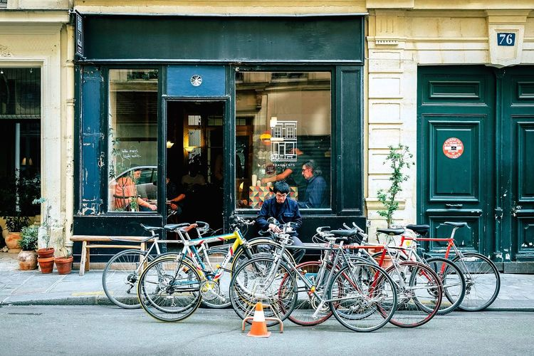 A man sits on a bench outside of a coffee shop on a Paris street, as a group of bikes rest by the curb on the asphalt. Paris, France  Paris Arondissement Street Cone EyeEm Best Shots Coffee Shop Bikes Bike Building Exterior Built Structure Architecture Window Bicycle Day Entrance Door Outdoors Building Glass - Material Mode Of Transportation Store Transportation Land Vehicle Shopping