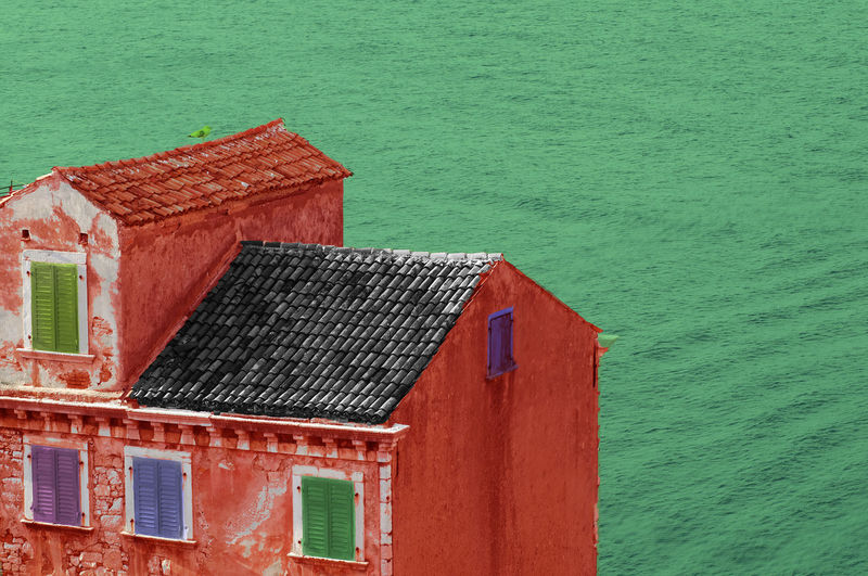 Red house by sea against building