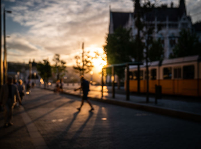 People walking on street in city during sunset