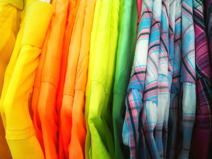 Close-Up Of Colorful Shirts Hanging In Closet