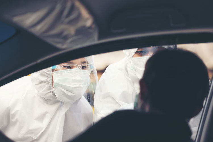 Asian woman drive thru covid-19 testing with ppe medical staff, covid testing temp while checking