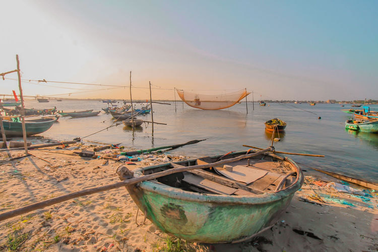 Fishing boats moored on sea against sky