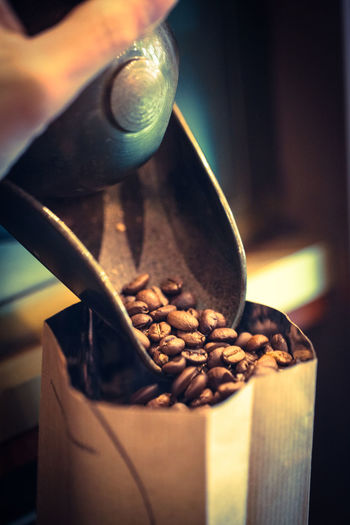 Cropped Image Of Hand Pouring Roasted Coffee Beans In Paper Bag