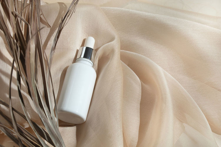 High angle view of moisturizer on textile