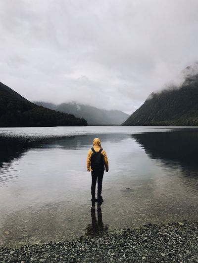 Full length of person with backpack standing in lake against sky
