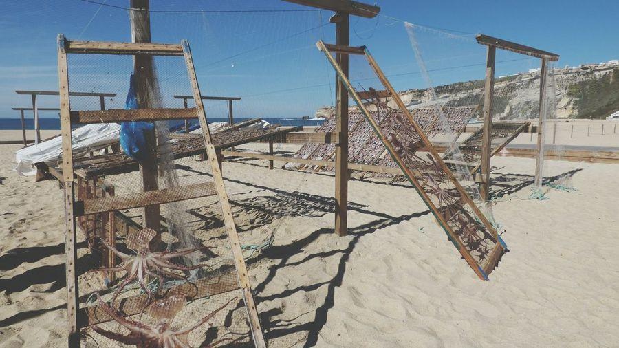 Fishing nets on beach against sky