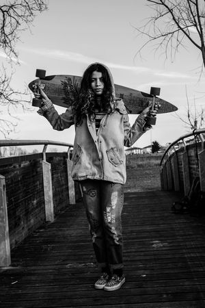 Women Around The World Front View Looking At Camera Long Hair One Person Standing Portrait Beautiful Woman Young Women Full Length Smiling Young Adult Leisure Activity Happiness Outdoors Lifestyles Sky Arms Outstretched Cheerful Day Real People Longboard Welcome To Black