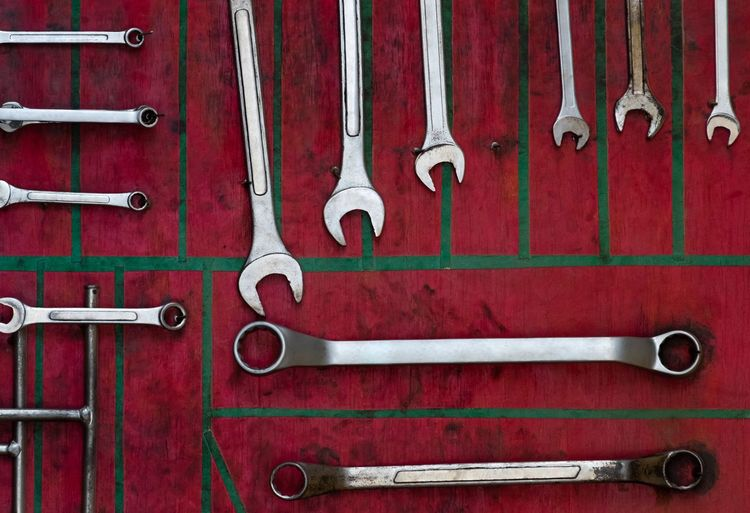 Various Work Tools Hanging On Red Wall In Workshop