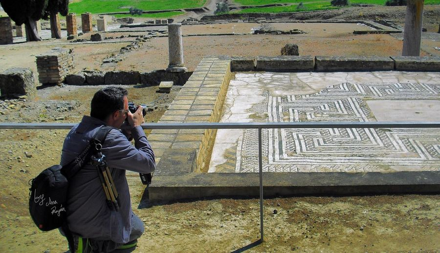Mosaic Romanos Ciudad Romana Italica Monument Real People Lifestyles Leisure Activity One Person Architecture Text Technology Side View Photography Themes Photographing Nature Built Structure Outdoors Men Communication Standing Three Quarter Length Casual Clothing Activity Day