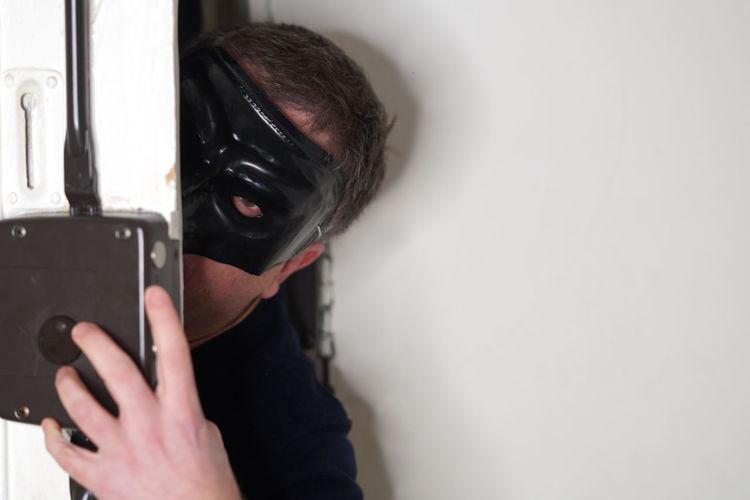 Close-up of thief opening door