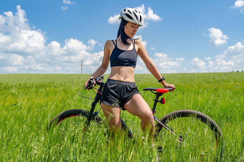 Young woman riding bicycle on field
