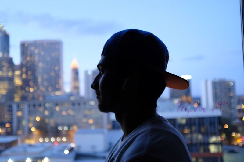 Close-up of man in city against sky at night