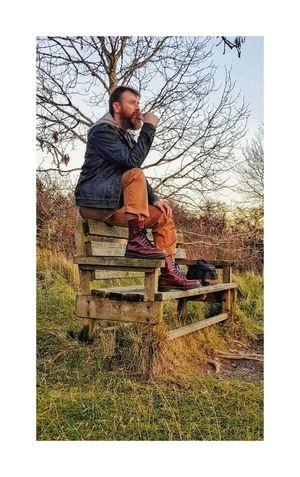 ponderings EyEm Selects Sitting Sitting Outside Sitting On A Bench Thinking Pondering Colourful Resting Tree Englishcountryside Men Full Length Senior Adult Males  Portrait Senior Men Sitting Sky Grass Auto Post Production Filter Tree Trunk Farmland