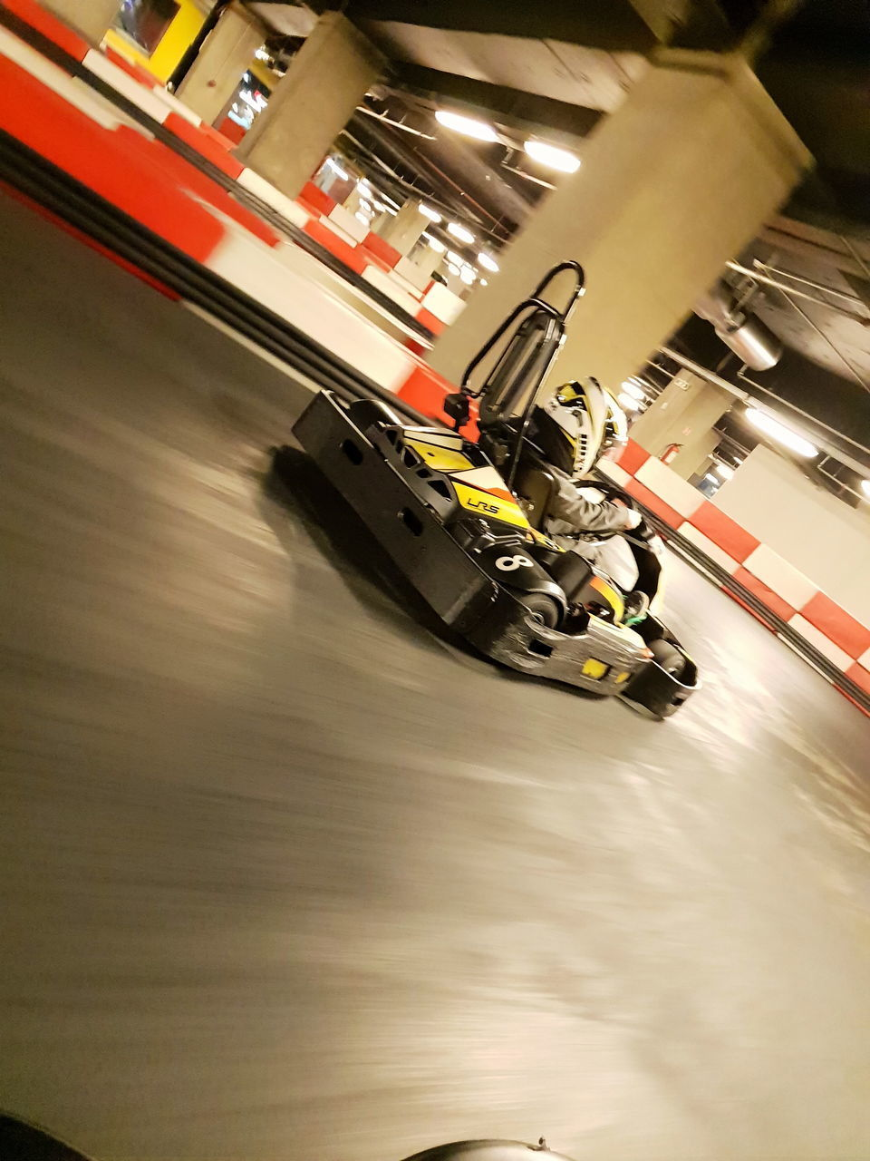 motion, mode of transportation, indoors, transportation, speed, blurred motion, high angle view, technology, flooring, land vehicle, on the move, selective focus, machinery, sport, occupation, equipment, car, illuminated, no people, toy, production line