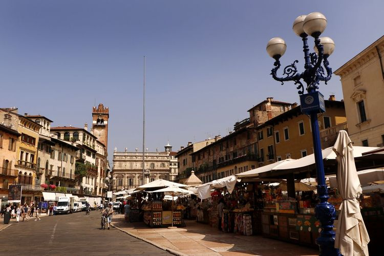 Market stalls in the Piazza delle Erbe in Verona, Italy Historical Building Travel Photography Architecture Building Building Exterior Built Structure City Clear Sky Crowd Day Incidental People Lighting Equipment Market Stall Marketplace Outdoors Piazza Piazza Delle Erbe Residential District Street Street Light Tourist Destination Travel Destination Urban Vacation Destination