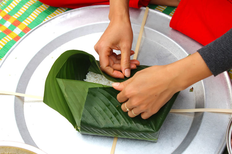 Midsection of woman wrapping food in leaves on tray