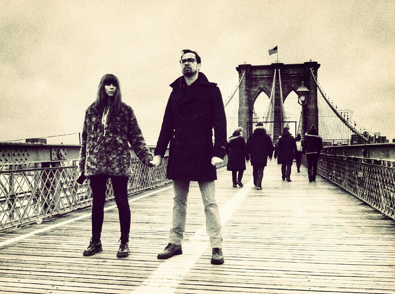 Couple holding hands on footbridge against sky