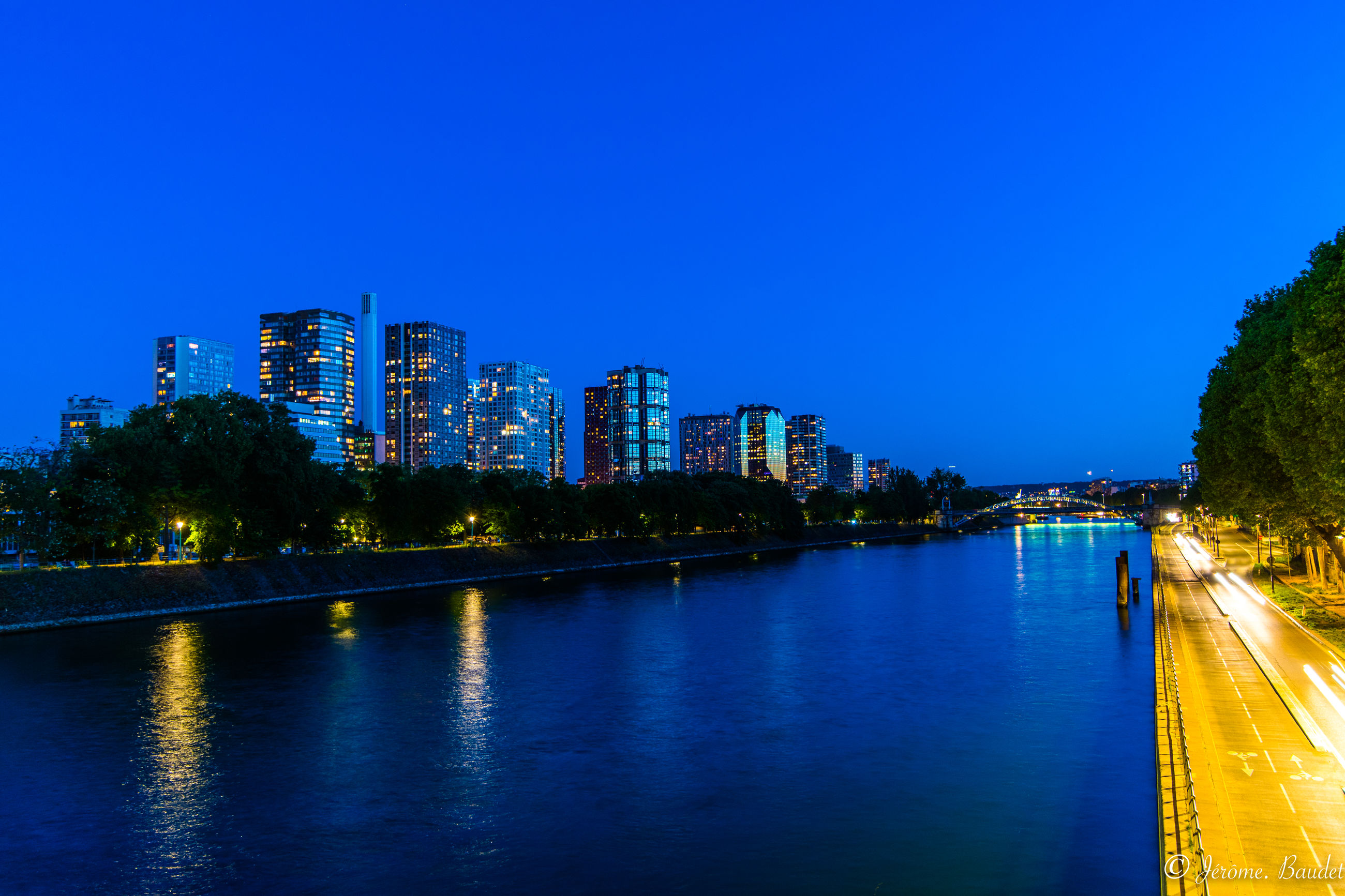 water, architecture, building exterior, built structure, sky, city, blue, illuminated, waterfront, building, nature, tree, river, reflection, no people, clear sky, night, plant, dusk, outdoors, cityscape, office building exterior, skyscraper