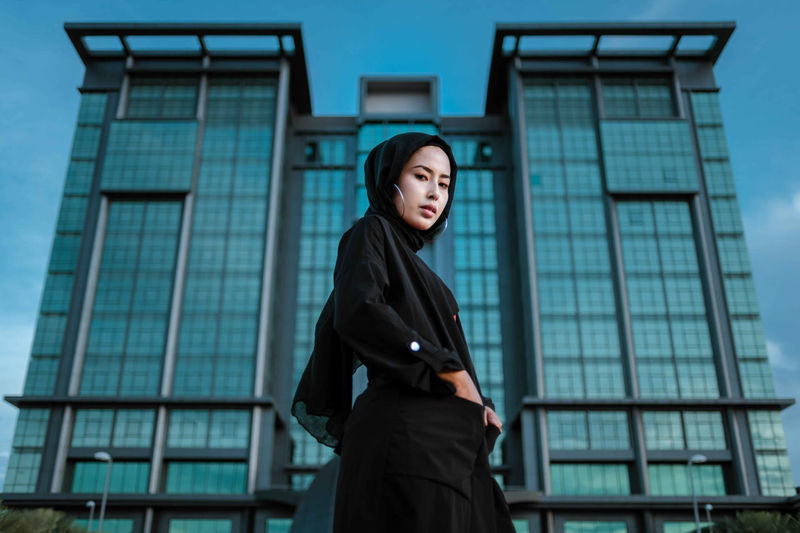Portrait of young woman standing against building