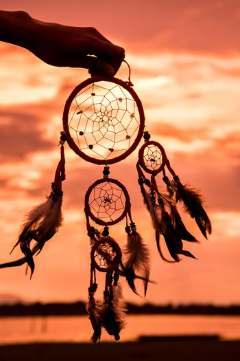 Cropped Hand Holding Dreamcatcher Against Orange Sky