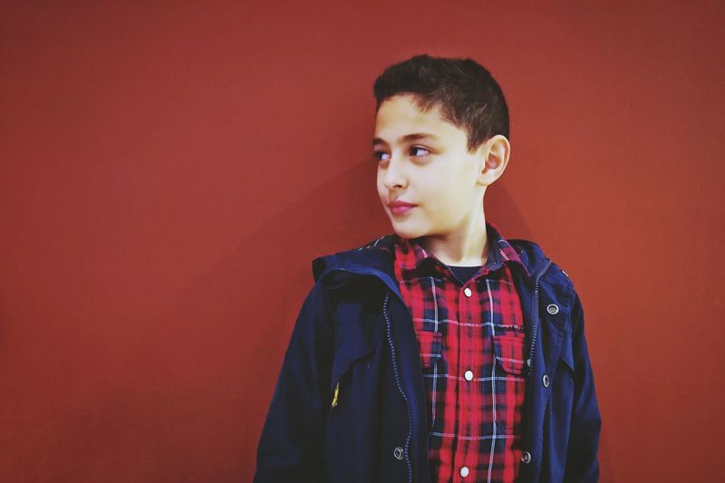 Cute Boy Standing Against Red Background