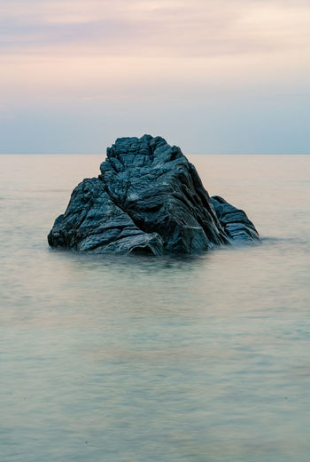 Stone in the water taken by long  exposure at sunset time