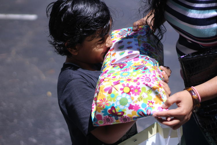 Midsection of woman giving gift to boy while standing on footpath