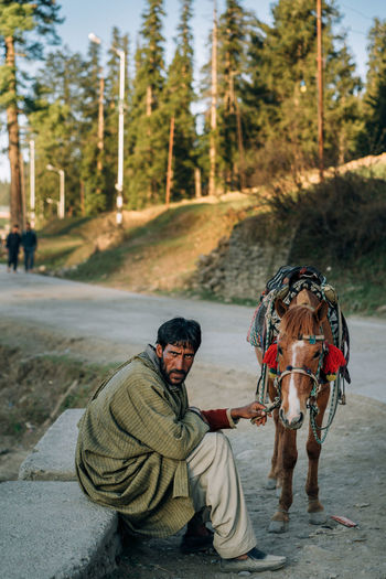 Man riding horse cart in forest