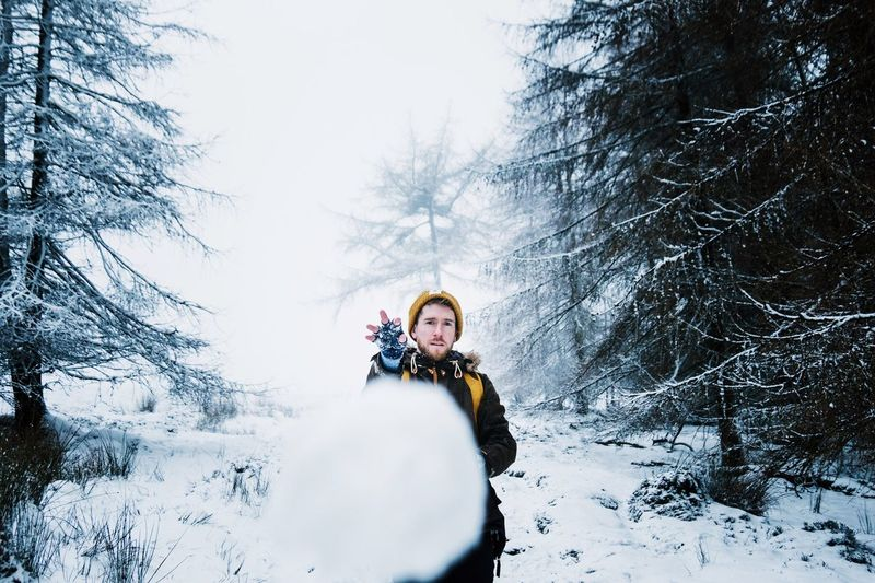 Man Throwing Snowball at camera Winter Snow Cold Temperature Warm Clothing Weather Outdoors One Person Tree Nature Looking At Camera Fun Young Adult Day Portrait Forest Snowball