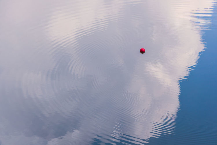 Ripples, reflection and a floating ball? Water Reflection No People Rippled Beauty In Nature Lake High Angle View Floating On Water Tranquil Scene Scenics - Nature Sky Cloud - Sky Clouds And Sky Water Reflections Tranquility Day Outdoors Floating Buoy Red Nature