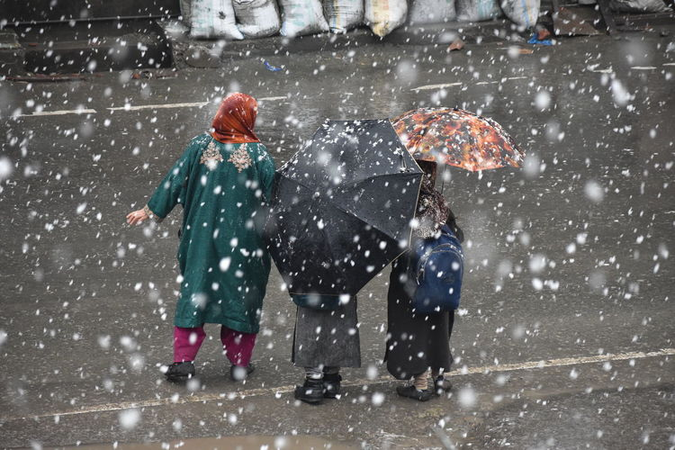 People with umbrella standing on road during snowfall