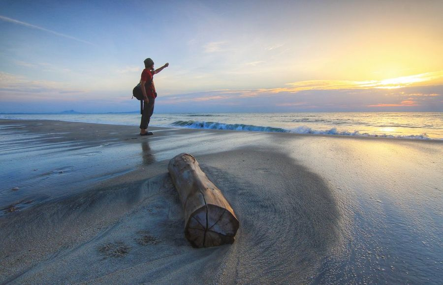 The wood left and a man at beach with a nice sunrise Sea Water Beach Men Sand Beauty Sky Horizon Over Water Landscape Low Tide Seascape Wave