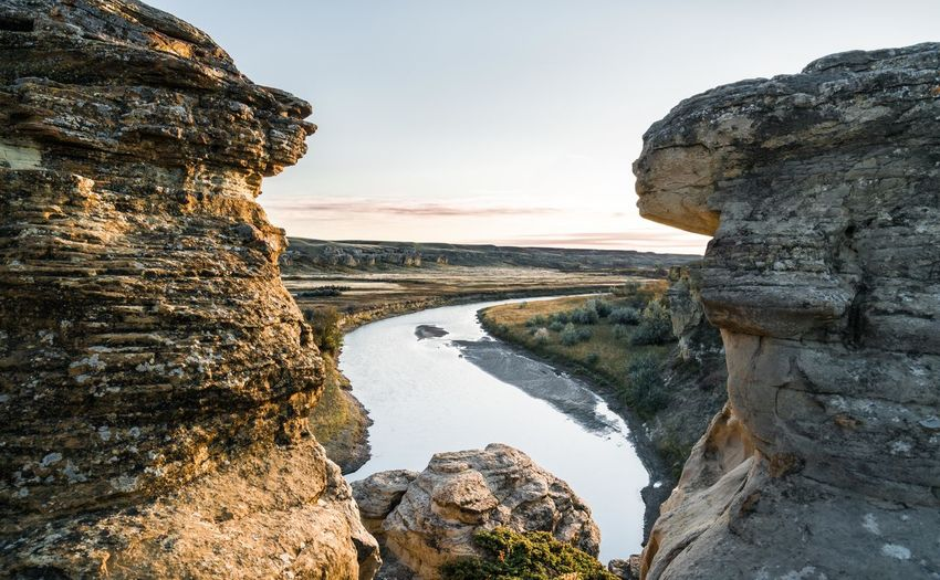 Scenic view of river and rock formation against sky during sunset