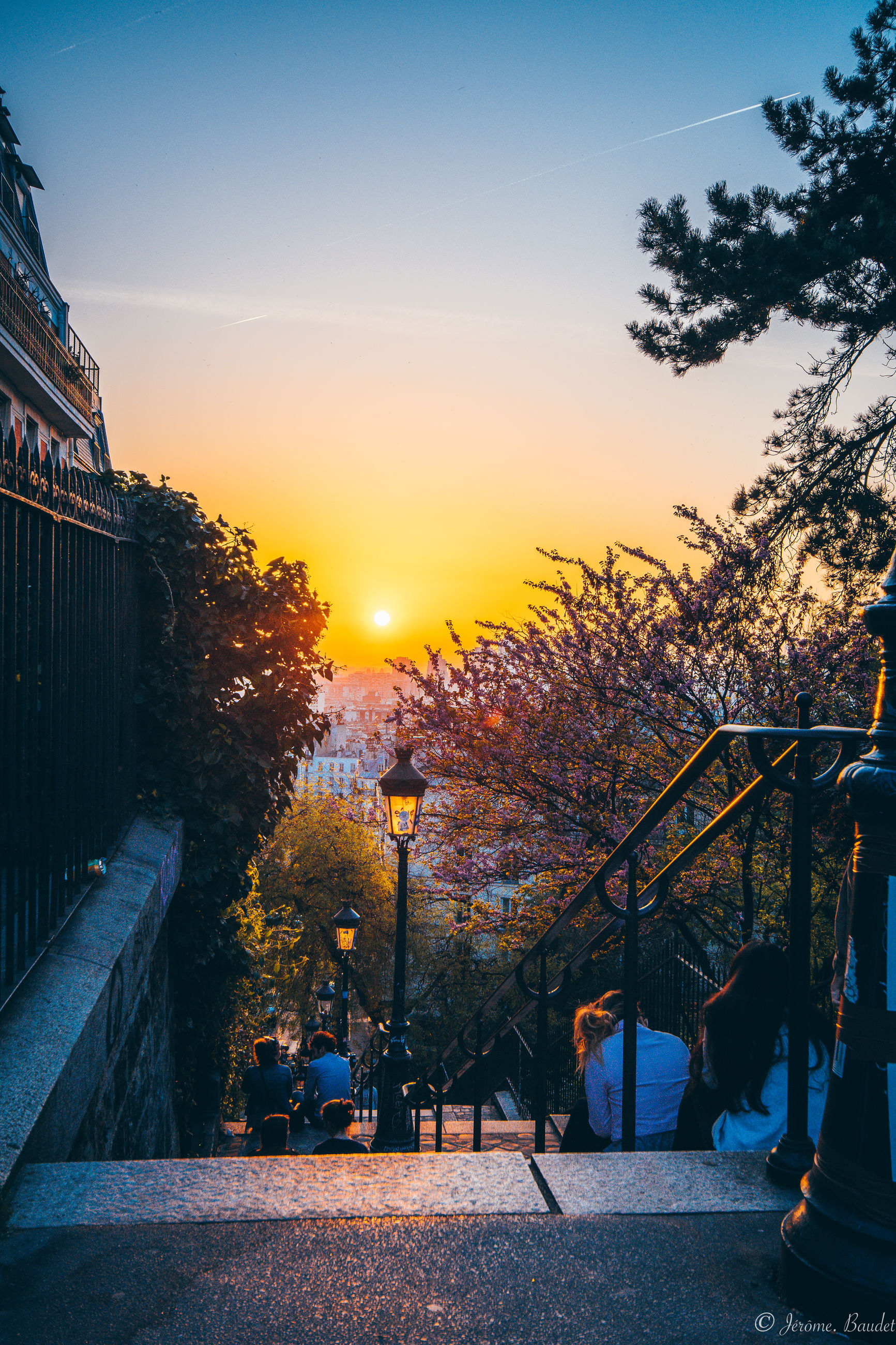 sunset, sky, tree, orange color, plant, architecture, building exterior, nature, city, street, built structure, outdoors, transportation, real people, mode of transportation, sunlight, motor vehicle, illuminated, beauty in nature, silhouette